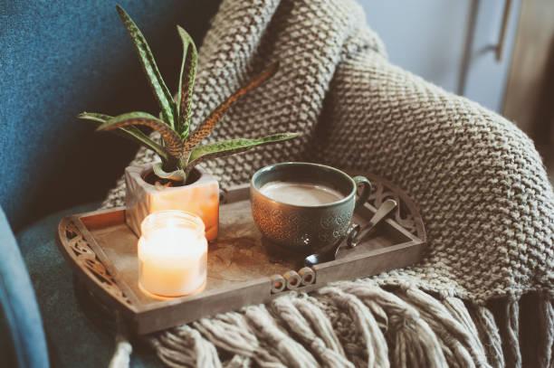 wintermorgen zu hause gemütlich. heißer kakao oder kaffee mit kerze auf blauen nordischen stil stuhl - herbst kerzen stock-fotos und bilder