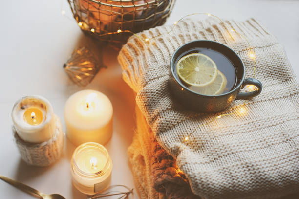 cozy winter morning at home. hot tea with lemon, knitted sweaters and modern metallic interior details. still life composition, danish hygge concept - hygge imagens e fotografias de stock