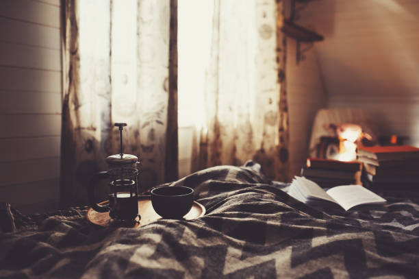 cozy winter morning with cup of hot tea. Nordic bedroom interior in country wooden house or cabin, hygge concept stock photo