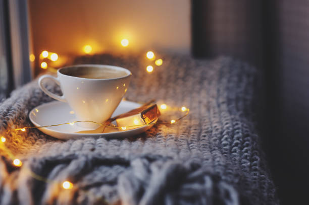 cozy winter or autumn morning at home. hot coffee with gold metallic spoon, warm blanket, garland and candle lights, swedish hygge concept. - hygge imagens e fotografias de stock