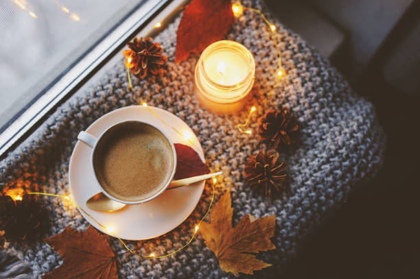 gemütliche winter oder herbst morgen zu hause. heißen kaffee mit gold metallic löffel, warme decke, garland und kerze lichter, schwedische hygge konzept. - fensterdeko herbst stock-fotos und bilder