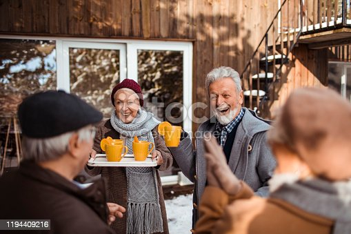 Close up of a group of seniors having hot tea while enjoying time together on the porch during winter