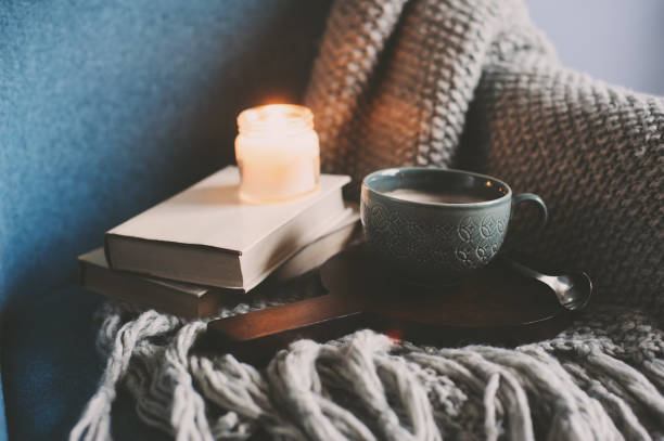 Cozy winter weekend at home. Morning with coffee or cocoa, books, warm knitted blanket and nordic style chair. Hygge concept. stock photo