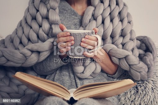 istock Cozy Woman covered with warm soft merino wool blanket reading a book. Relax, comfort lifestyle. 889146982