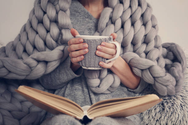 Cozy Woman covered with warm soft merino wool blanket reading a book. Relax, comfort lifestyle. stock photo