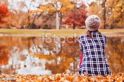 istock cozy woman sitting near autumn lake, beautiful fall landscape 881639238