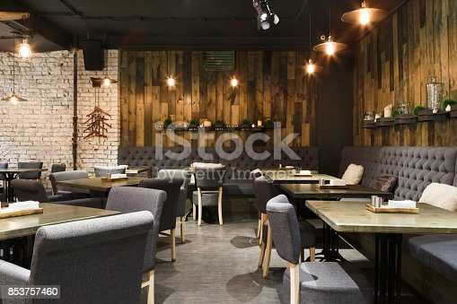 Cozy wooden interior of restaurant, copy space. Comfortable modern dining place, contemporary design background