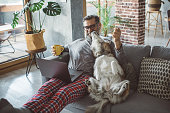 Mature men home in pajama spending cozy evening during isolation period, pet dog is with him. They sitting on sofa, man working on laptop