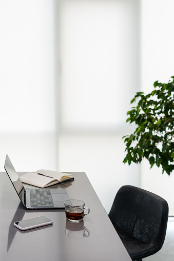 Glossy table with laptop and smartphone indoors, open notebook prepared to take notes, cup of black tea, leaves of greenery behind, light coming from big window with white curtain. Vertical shot