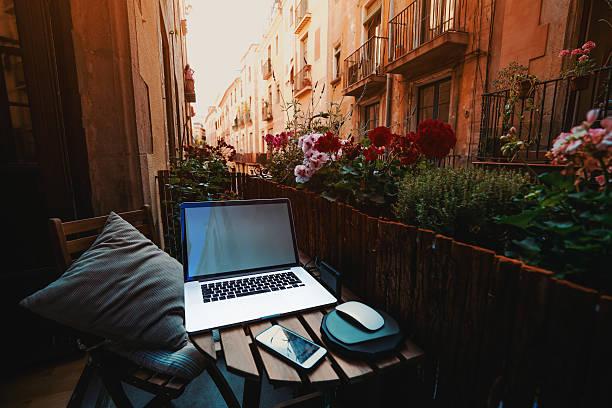 cozy workspace on balcony in barcelona - reiseblogger stock-fotos und bilder