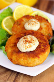A vertical image of two crab cakes on a white plate garnished with lemons and a dijon mustard sauce.