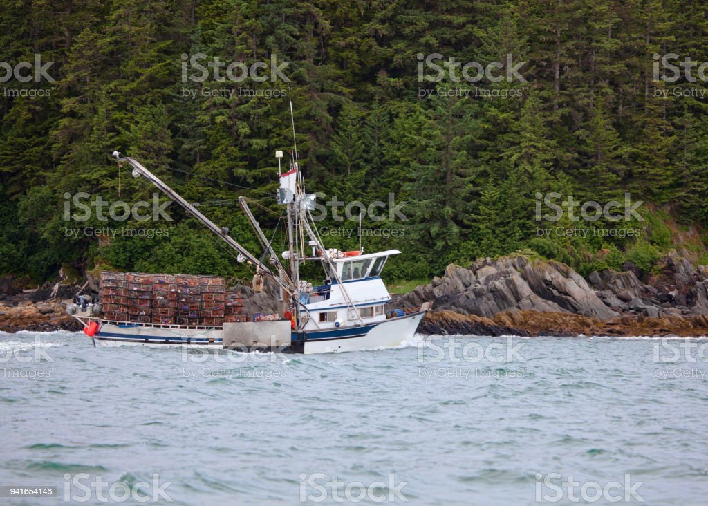 Crab fishing boat with empty crab pots in Southeast Alaska stock photo