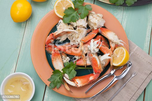 Assorted Dungeness crab legs with butter mustard sauce and fresh lemons..