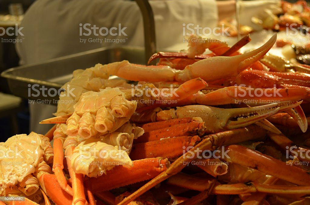 Crab Legs for Sale with Vendor in Background stock photo