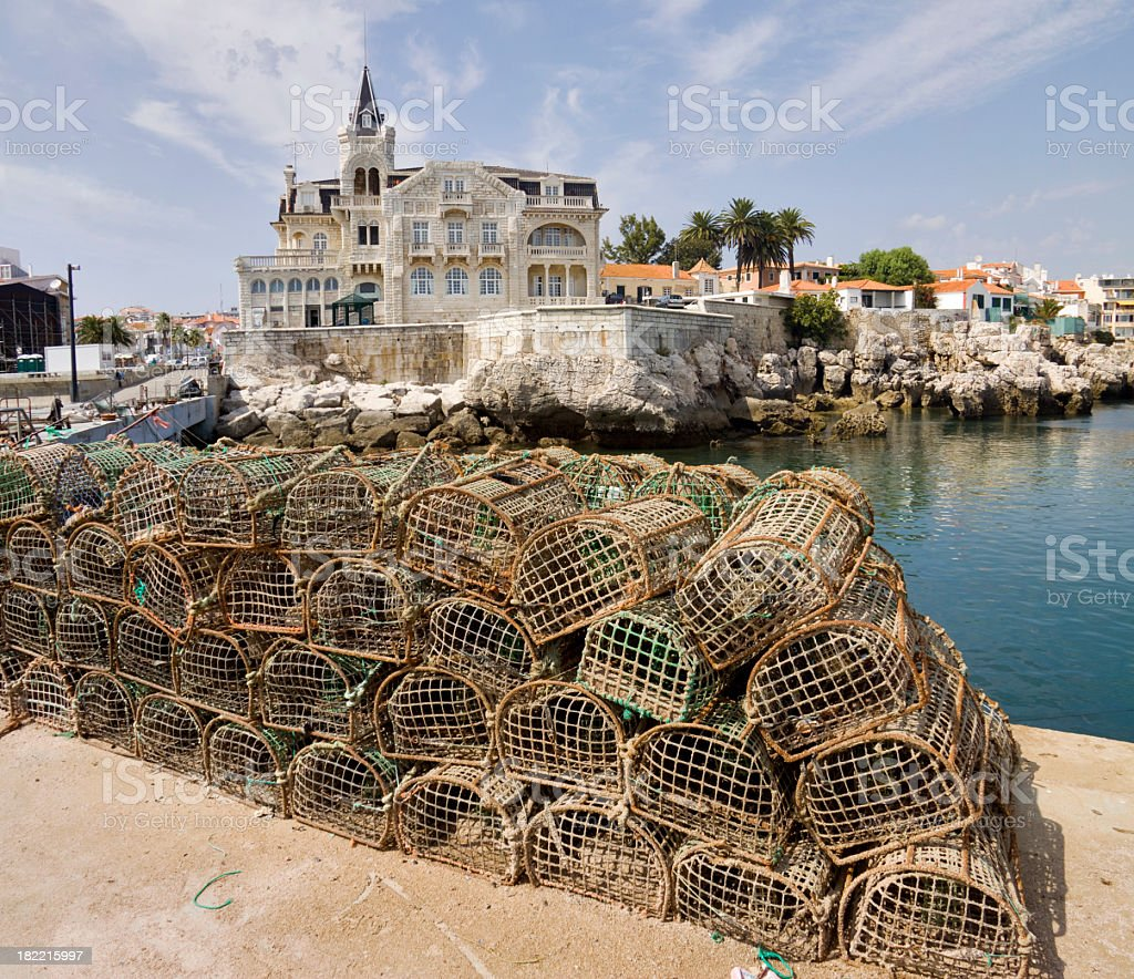Crabbing cages stacked by water with quaint town behind stock photo