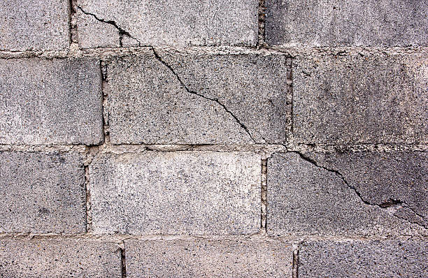 crack in concrete cinder block wall background.cement cinder block - stability stock photos and pictures