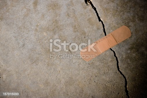 Adhesive bandage holding together a splitting concrete wall. (Concept: termporary solution) Tight/shallow DOF on bandage.