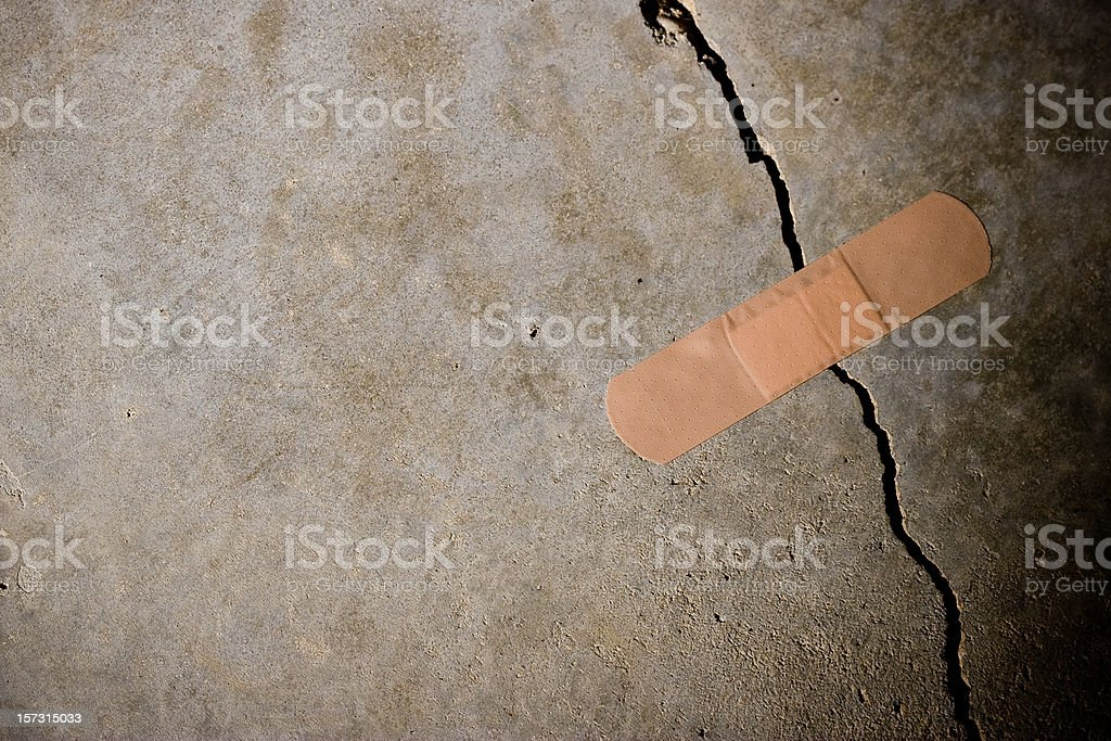 Crack in concrete with Band-Aid on top stock photo