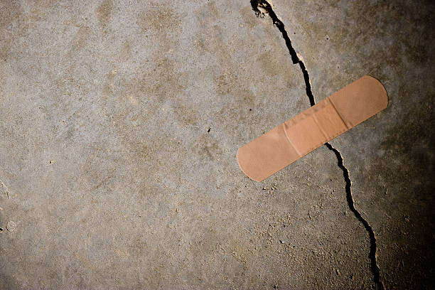 crack in concrete with band-aid on top - stability stock photos and pictures