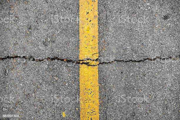Photo of Crack on line yellow on road textured