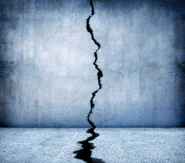 Crack Running Through Concrete Walls And Floor A large crack runs through the middle of a concrete floor and wall. apart stock pictures, royalty-free photos & images