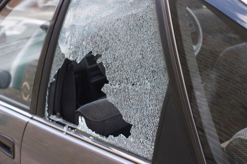 Cracked and crazed glass reveals the workings of a thief in the night, during the morning after. One more car crime in London.