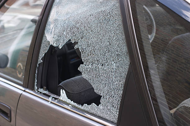 Thief broken glass in car window Cracked and crazed glass reveals the workings of a thief in the night, during the morning after. One more car crime in London. whiteway stock pictures, royalty-free photos & images