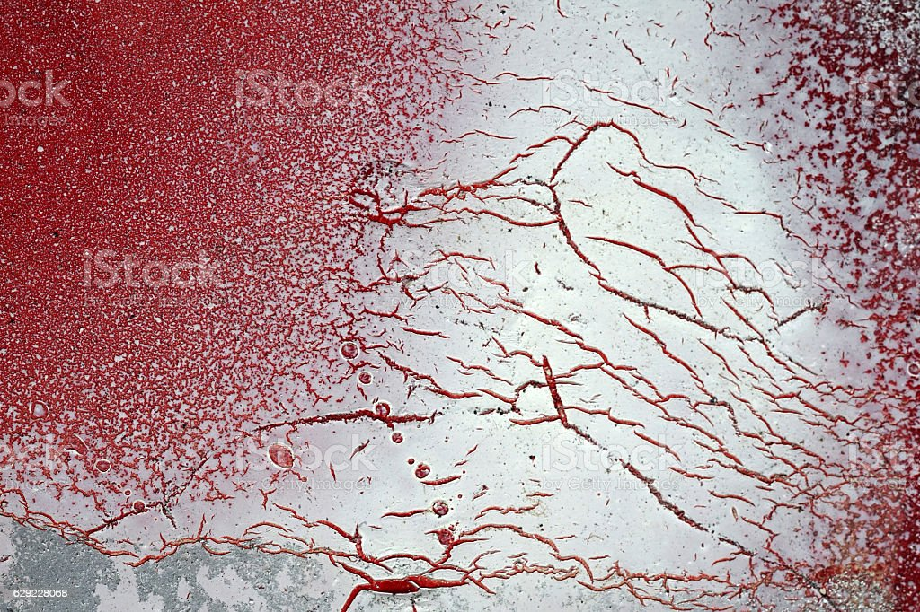 Cracked and scratched red and white paint on grunge metal stock photo