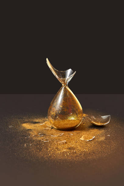 Cracked antique hourglass with golden sand on a black duotone background. stock photo