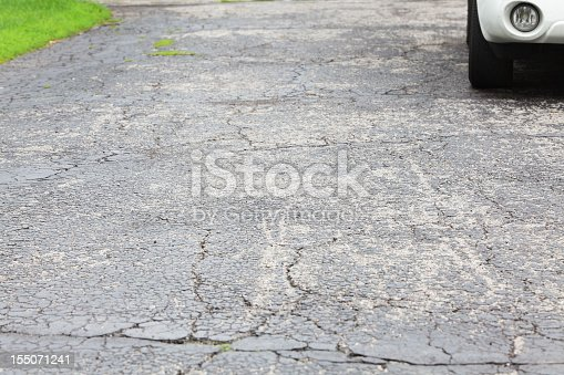 istock Cracked asphalt driveway with car parked 155071241