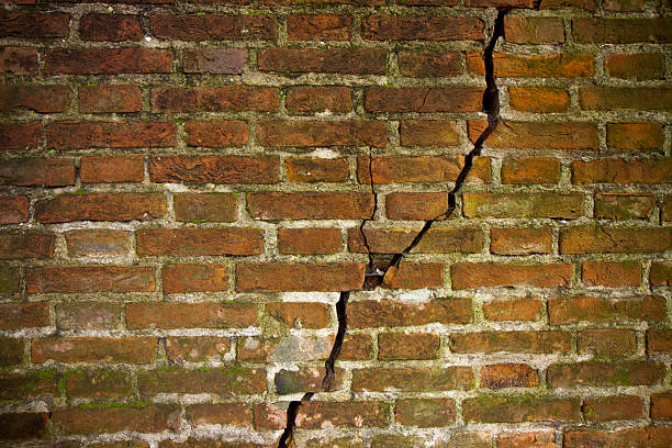 cracked brick wall - stability stock photos and pictures