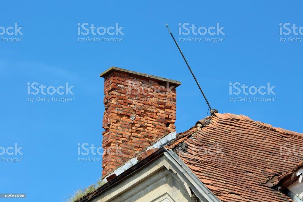 Gebrochene aus rotem Backstein Kamin neben Metall schiefen Blitzableiter auf verlassenen alten Gebäudedach geknackt – Foto