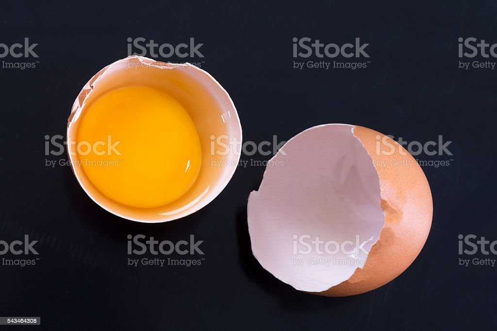 Cracked chicken egg on a black background stock photo