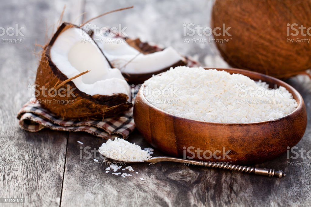 Cracked  coconut and flakes on rustic wooden table background stock photo