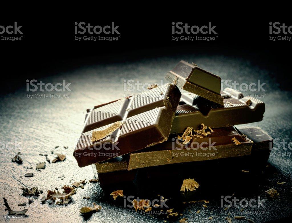 Cracked dark chocolate bar at black background, close up