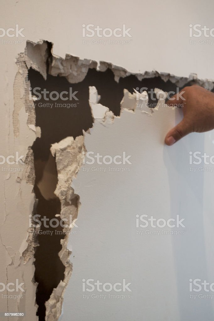 Cracked, destruction of a white wall stock photo