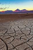 Cracked earth and Licancabur volcano at the Atacama Desert.