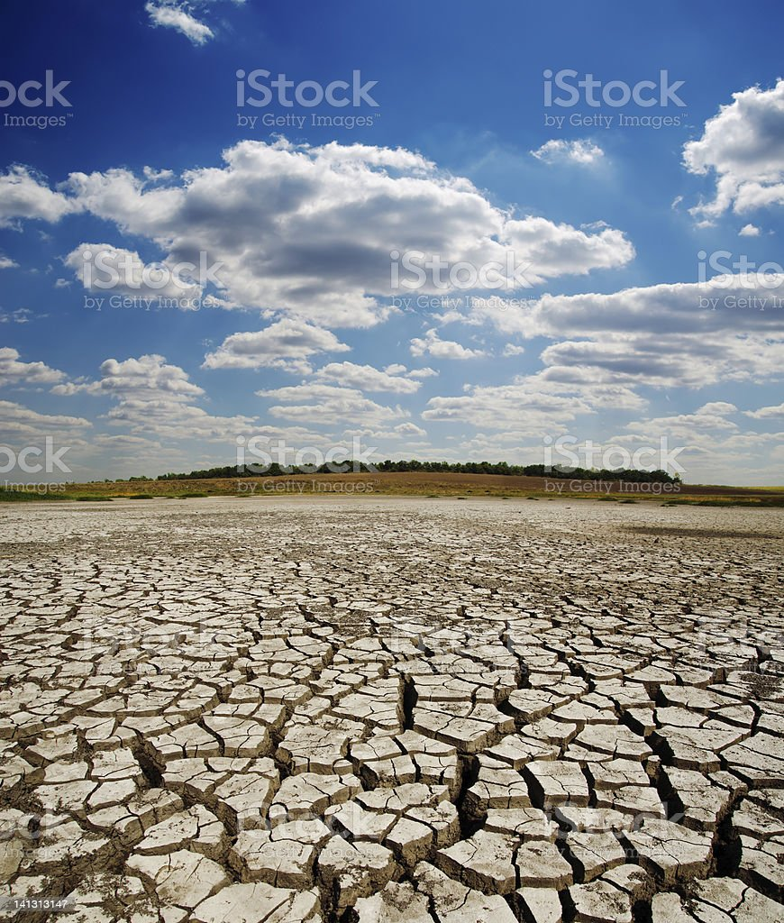 cracked earth under dramatic sky stock photo