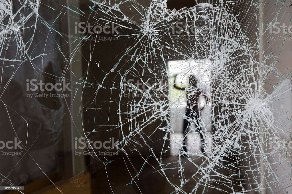 Cracked glass with outline of a person in the background royalty-free stock photo