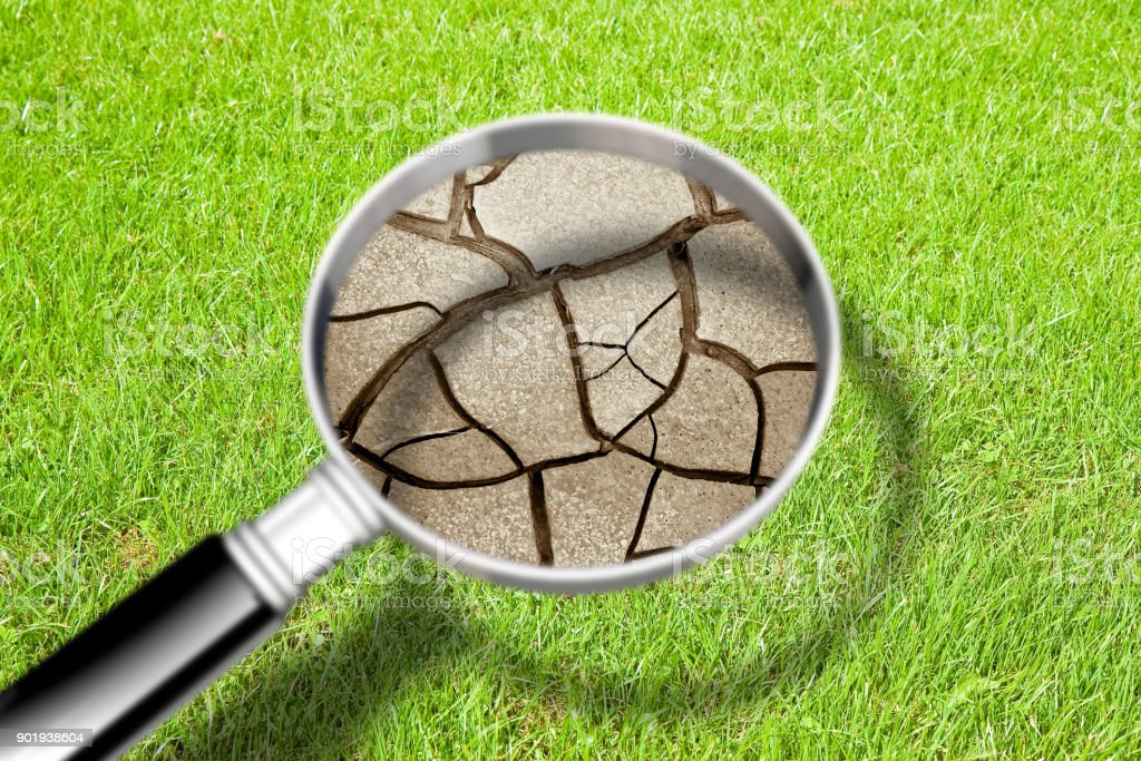 Cracked ground seen through a magnifying glass - The effects of drought - Concept image stock photo