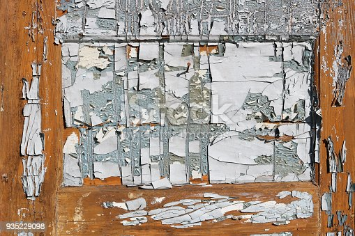 Cracked paint on an old wooden aged  door resembles an abstract painting. Outdoor  sunny day shot