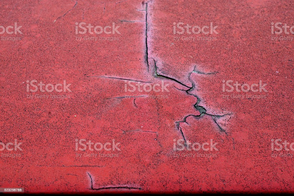 Cracked red paint on grunge metal surface - macro 1 stock photo