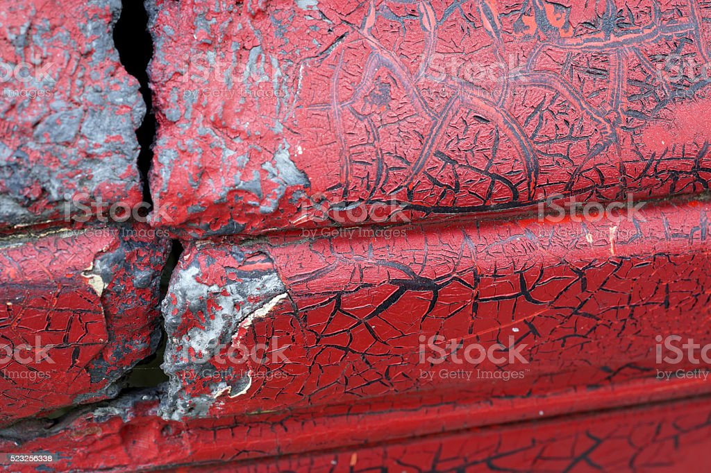 Cracked red paint on grunge metal surface - macro 2 stock photo