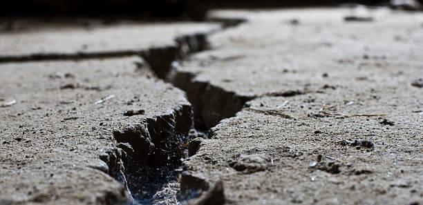 cracked road concrete close up - kaldırım stok fotoğraflar ve resimler