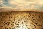 istock Cracked soil earth desert terrain with sky 607915748