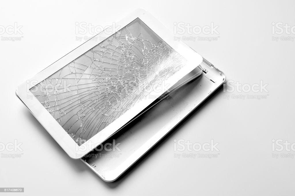 cracked tablet on white desk stock photo