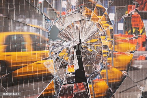 A New York City taxi is reflected in a cracked door window.