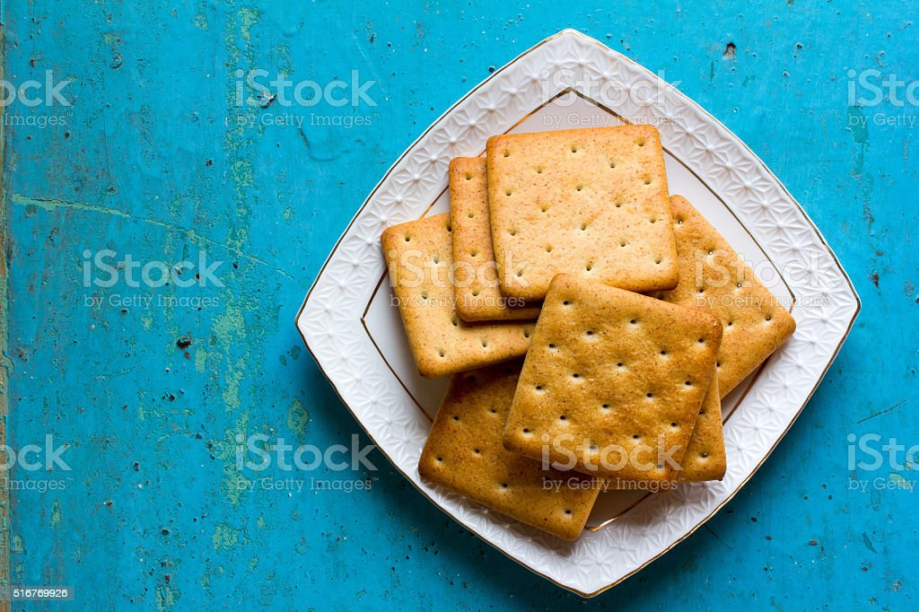 Cracker biscuits in a white ceramic square saucer stock photo