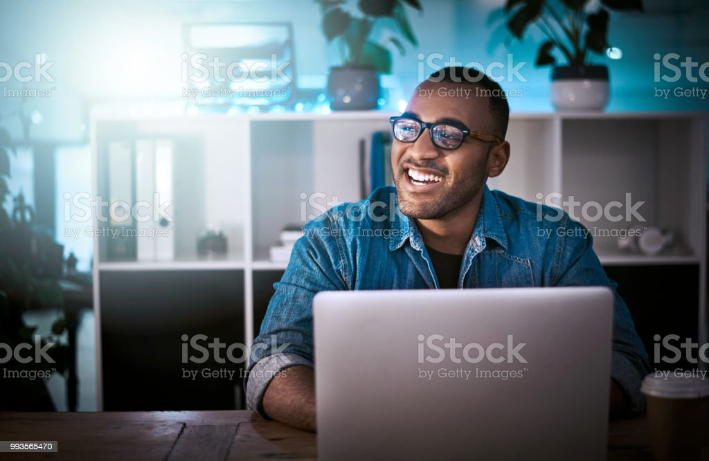 Cracking codes is my speciality Shot of a young designer working late on a laptop in an office 20-29 Years Stock Photo