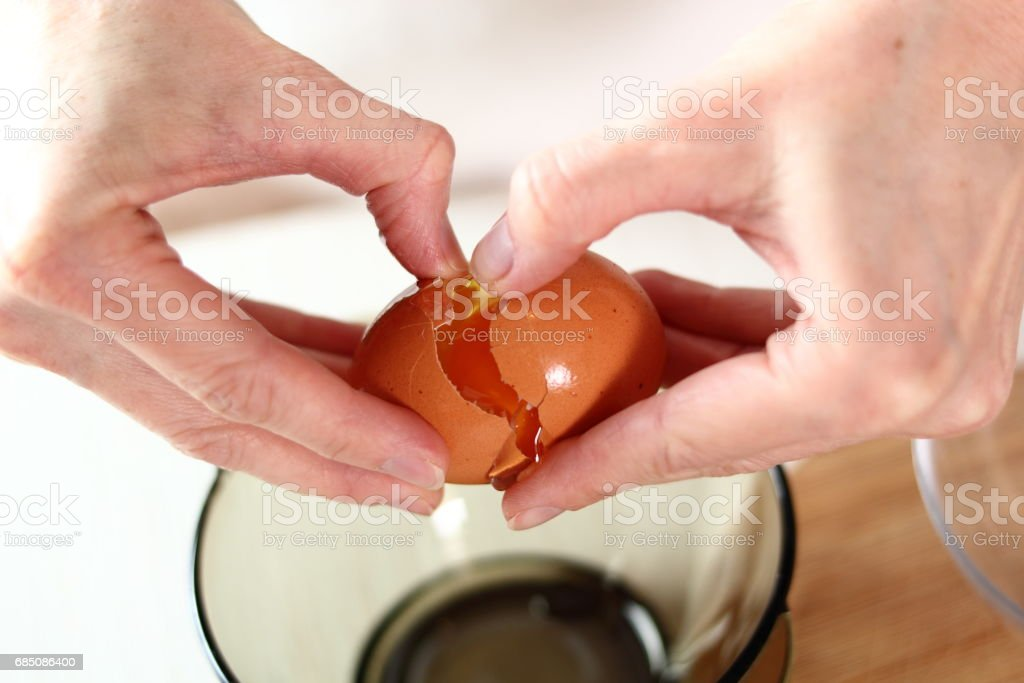 Cracking egg. Making frozen strawberry cheesecake series. royalty-free stock photo